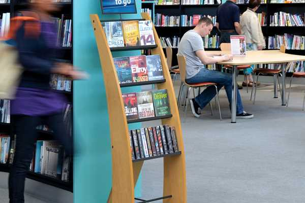 People and books on display in a busy public library